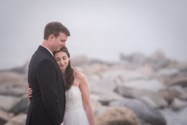 Bride and Groom hugging on rocks on beach in the fog