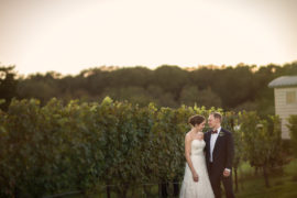 Bride & Groom standing together with vines behind them at golden hour