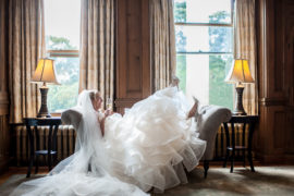 Bride in ballgown kicking up her heels and laughing while holding a glass of champagne in a wood paneled room