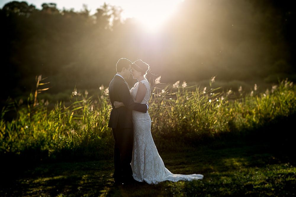 Bride and Groom hugging in front of tall sea grasses with sun flare behind