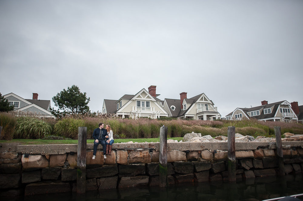 A couple sitting on a dock looking at the water