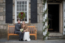Bride in a fur coat and Groom sitting on a bench with Christmas Decorations